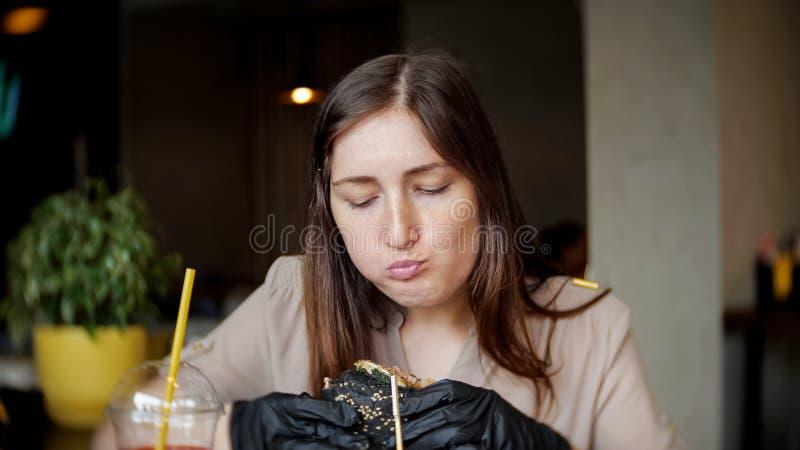 Menina bonita em luvas pretas que come um Hamburger no café imagem de stock royalty free