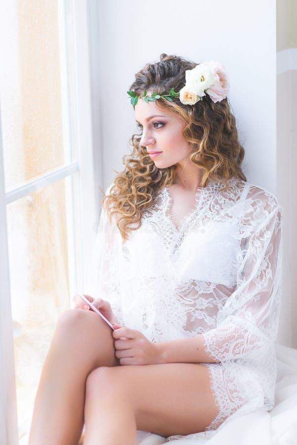 Menina bonita em um assento nupcial branco do négligé foto de stock