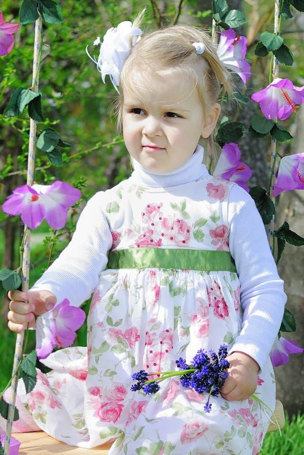 Menina bonita em um balanço em um vestido bonito imagens de stock royalty free