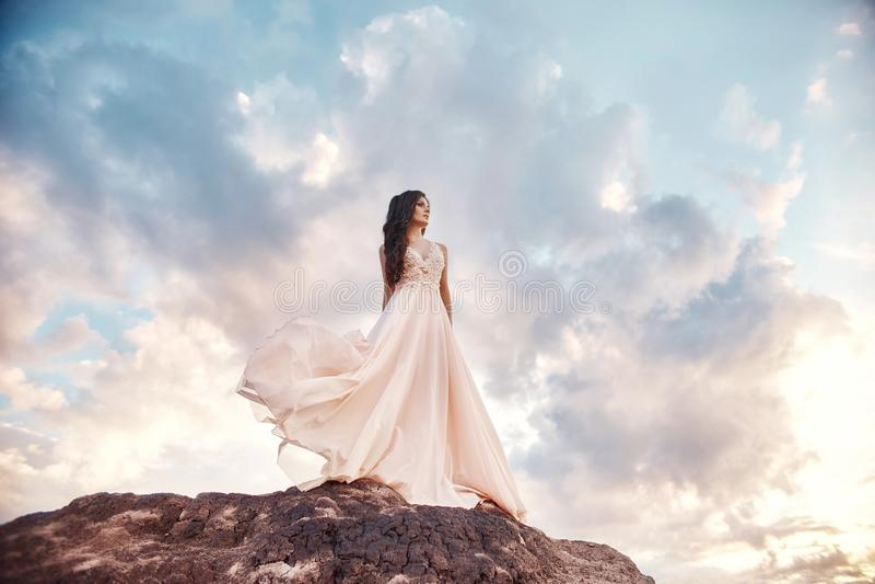 A menina bonita em um bege claro do vestido do verão anda nas montanhas O vestido leve vibra no vento, céu azul do verão fabulous foto de stock royalty free