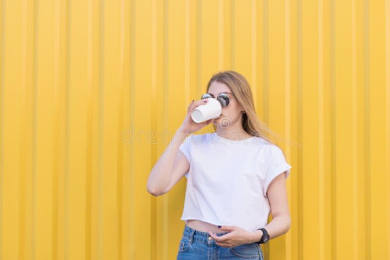 Menina bonita em um café bebendo da camisa branca dos copos de papel em um fundo da parede amarela foto de stock