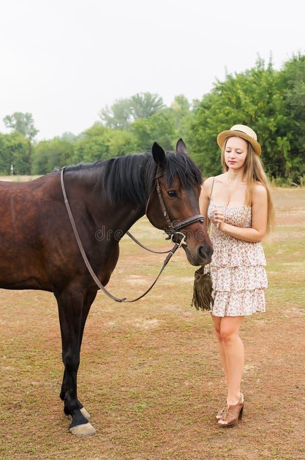 A menina bonita em um chapéu de palha e o verão vestem-se com um cavalo imagens de stock royalty free