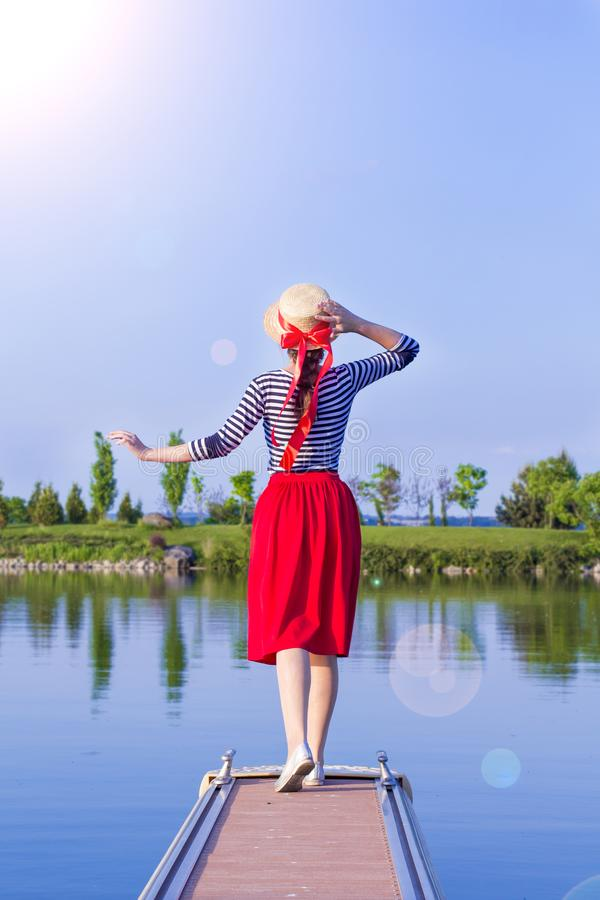 Menina bonita em um chapéu de palha no cais da parte traseira Menina em uma saia vermelha e um terno de marinheiro no cais no por fotos de stock