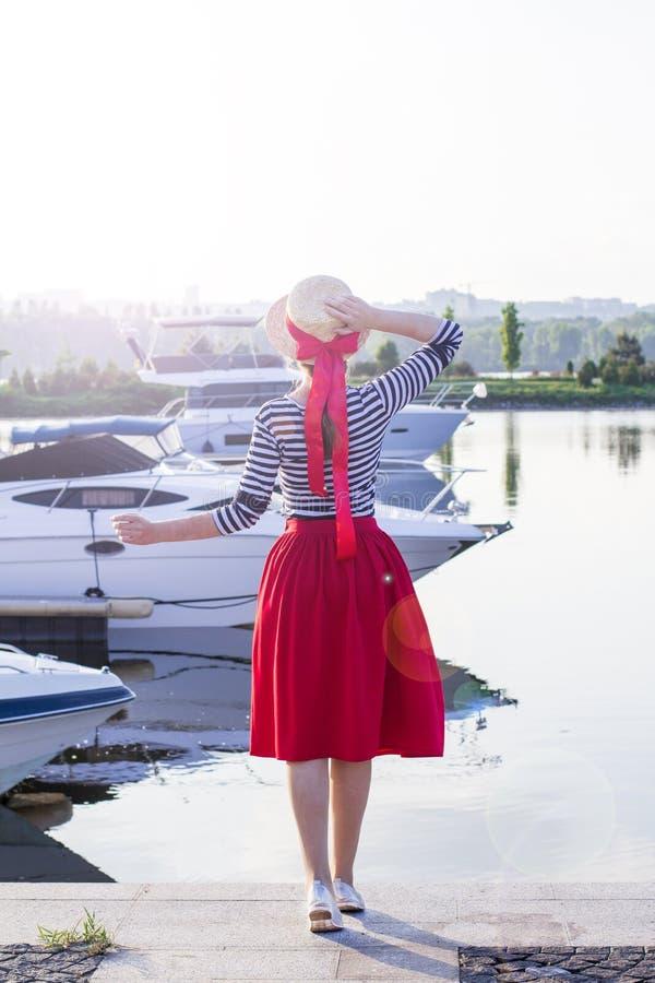 Menina bonita em um chapéu de palha no cais perto dos iate e dos barcos do mar Menina em uma saia vermelha e um terno de marinhei fotos de stock