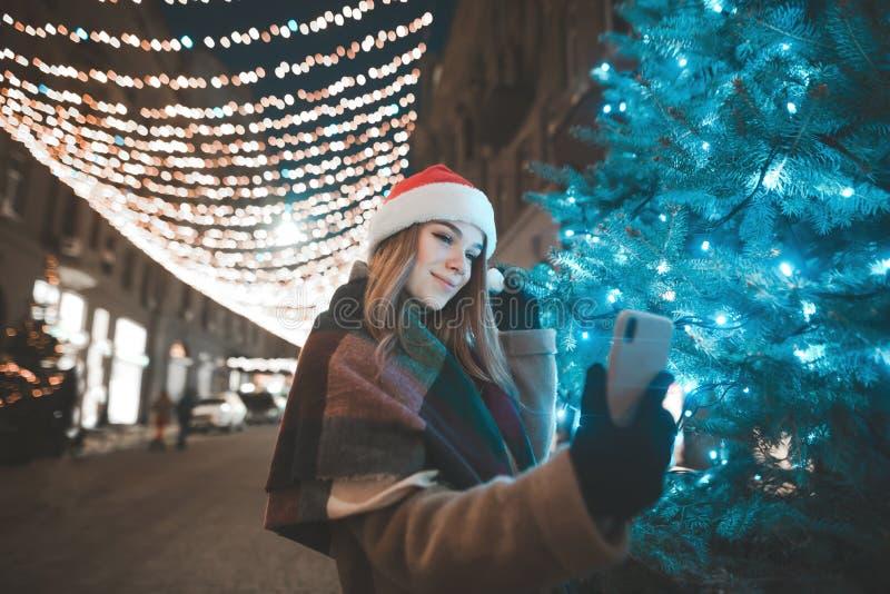 A menina bonita em um chapéu do Natal está na noite em uma rua perto de uma árvore de Natal e toma o selfie fotos de stock