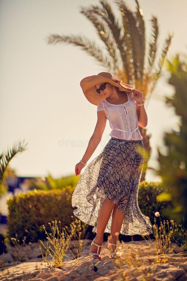 Menina bonita em um chapéu largo-brimmed em um fundo da palma tr imagem de stock