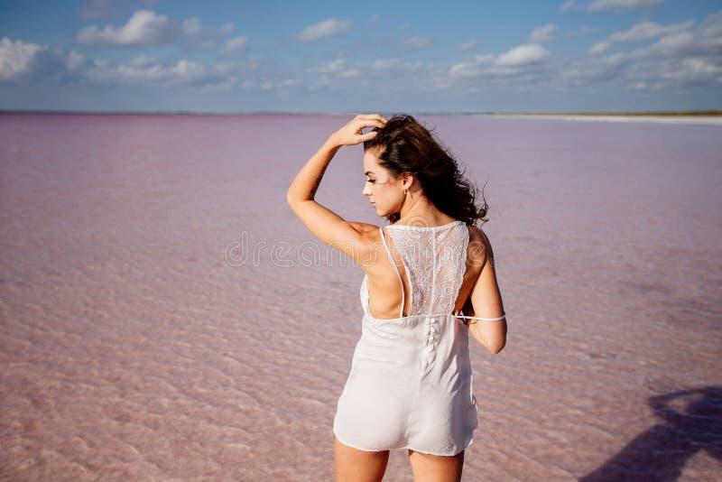 Menina bonita em um lago cor-de-rosa fotos de stock