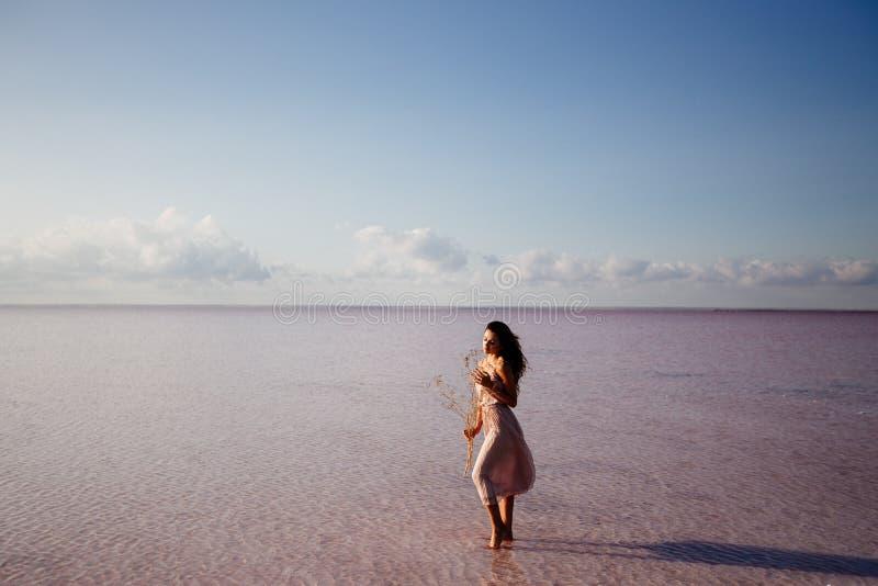 Menina bonita em um lago cor-de-rosa imagem de stock