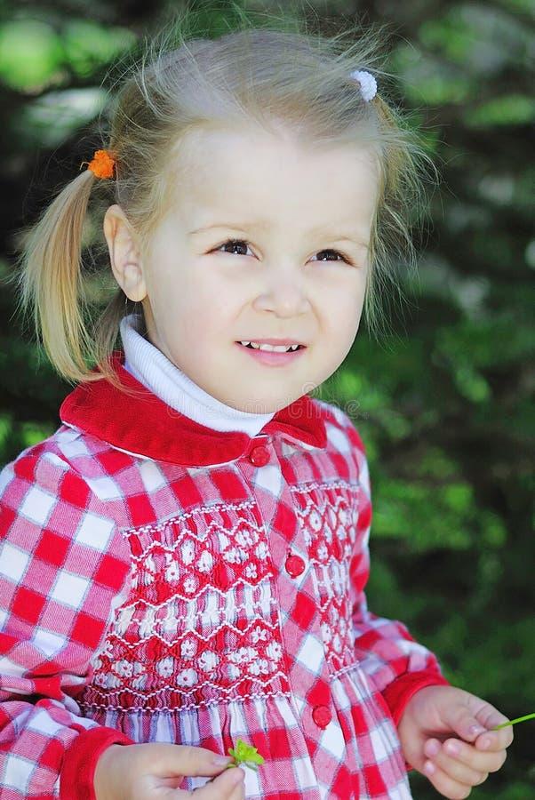 Menina bonita em um prado verde em um vestido vermelho bonito foto de stock royalty free