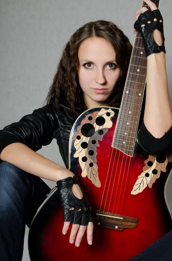 Menina bonita em um revestimento de couro com uma guitarra fotografia de stock royalty free