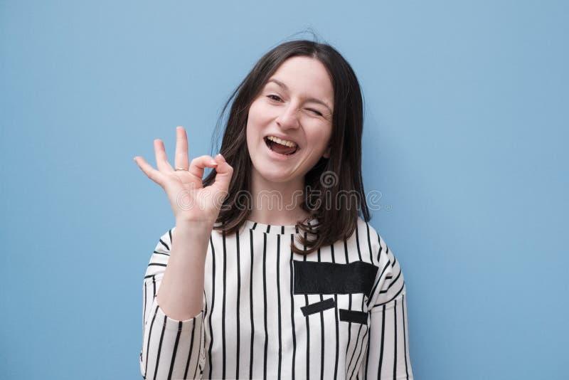 A menina bonita em um t-shirt listrado está contra um fundo azul da parede fotografia de stock