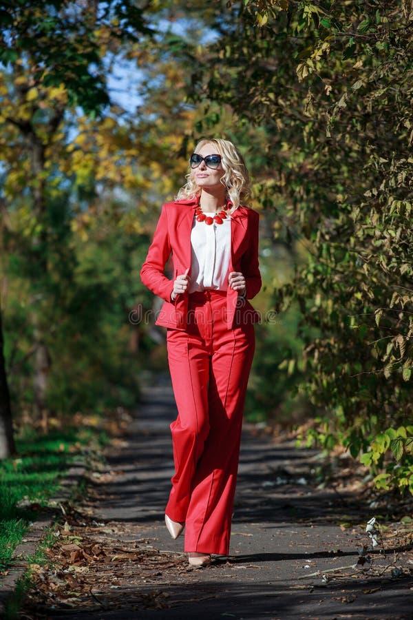 Menina bonita em um terno vermelho no outono imagens de stock royalty free