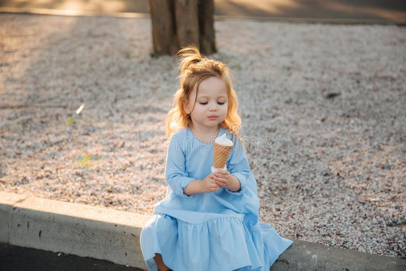 Menina bonita em um vestido azul que come um gelado foto de stock