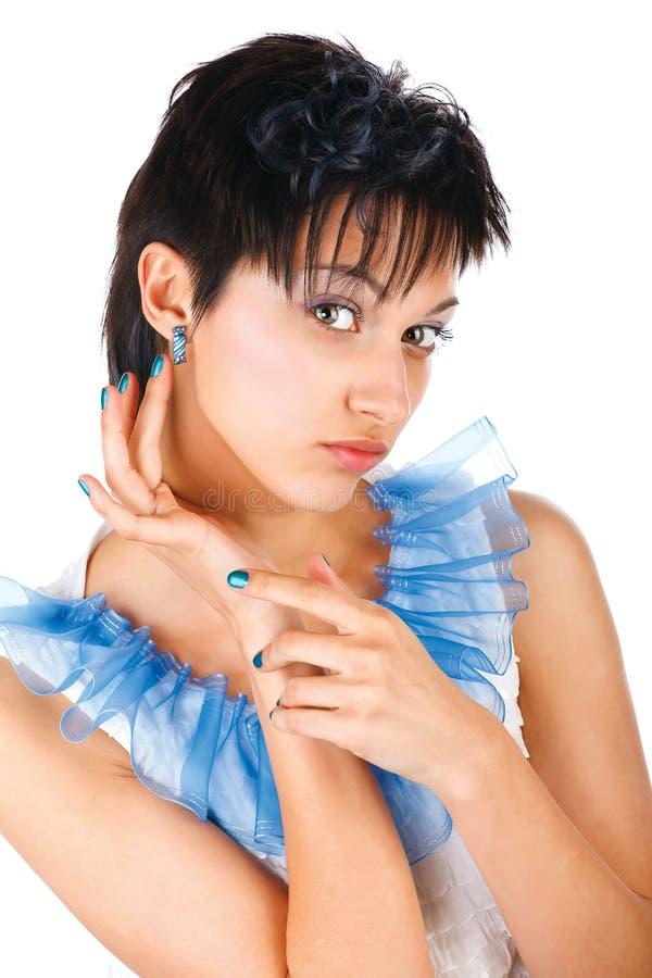 Menina bonita em um vestido branco com pregos azuis fotografia de stock royalty free