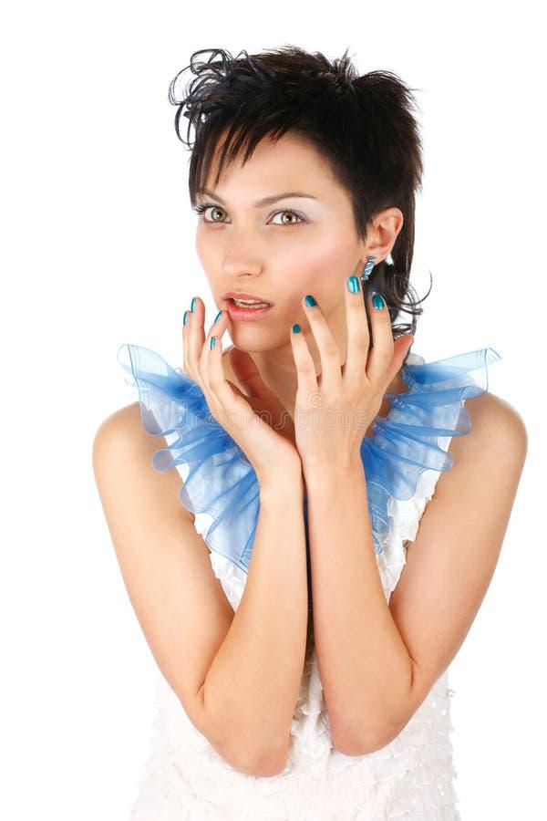 Menina bonita em um vestido branco com pregos azuis imagens de stock royalty free