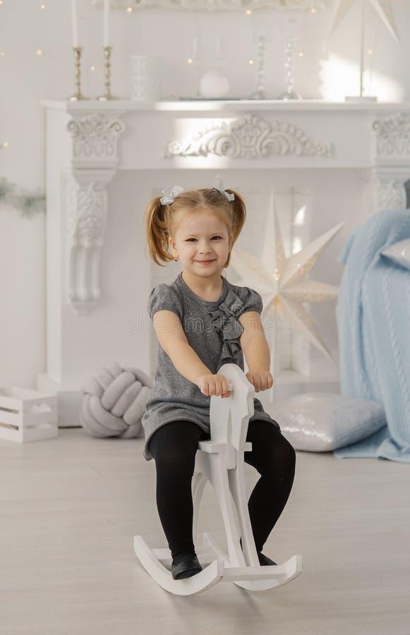 A menina bonita em um vestido branco como uma princesa está sentando-se em um cavalo de madeira do brinquedo em um estúdio do vin fotos de stock