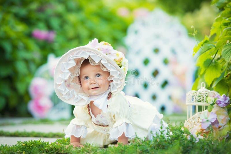 A menina bonita em um vestido branco e o chapéu em uma mola jardinam imagem de stock royalty free