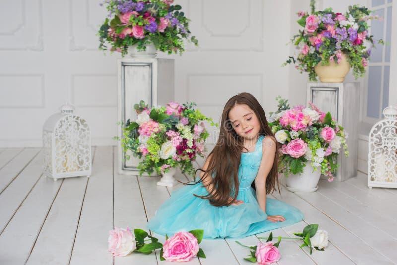 A menina bonita em um vestido de turquesa senta e joga com flores em um assoalho imagens de stock