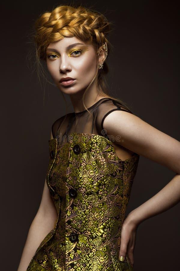 Menina bonita em um vestido do ouro com composição criativa e tranças em sua cabeça A beleza da cara imagem de stock royalty free