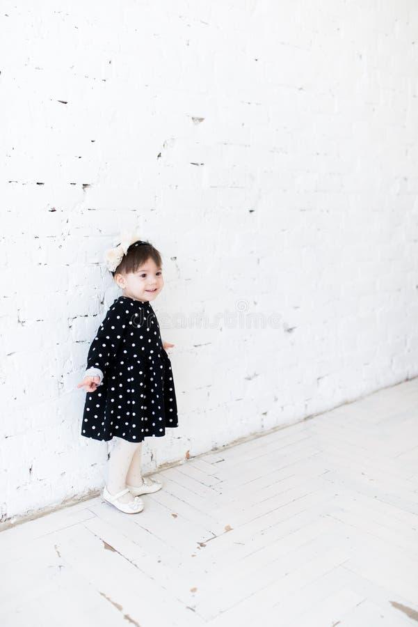 A menina bonita em um vestido do ?s bolinhas est? estando perto da parede e do sorriso brancos de tijolo Celebra??o do anivers?ri imagens de stock