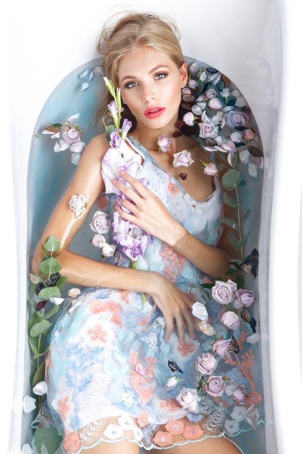 Menina bonita em um vestido do verão no banheiro com flores Face da beleza imagens de stock royalty free