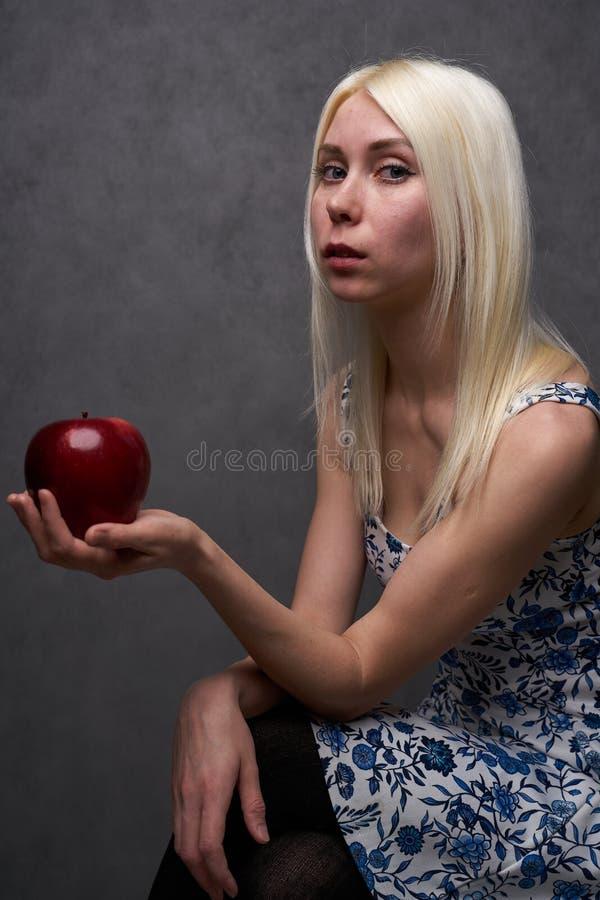 Menina bonita em um vestido elegante com maçã foto de stock royalty free