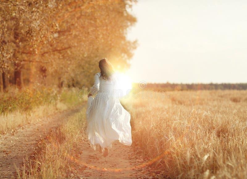 Menina bonita em um vestido no por do sol imagem de stock