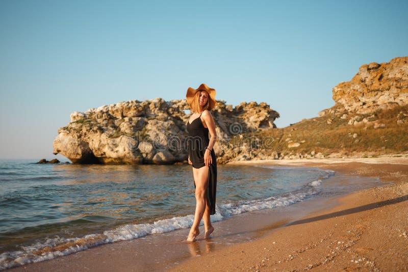 Menina bonita em um vestido preto e em caminhadas do chapéu ao longo da costa arenosa do mar no por do sol imagens de stock