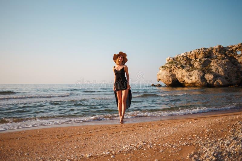 Menina bonita em um vestido preto e em caminhadas do chapéu ao longo da costa arenosa do mar no por do sol foto de stock royalty free