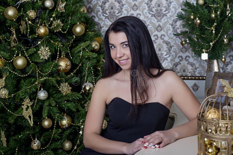 Menina bonita em um vestido preto no fundo da árvore de Natal fotografia de stock royalty free