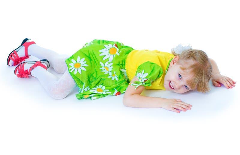 Menina bonita em um vestido verde com margaridas, mentiras na A.A. fotografia de stock royalty free