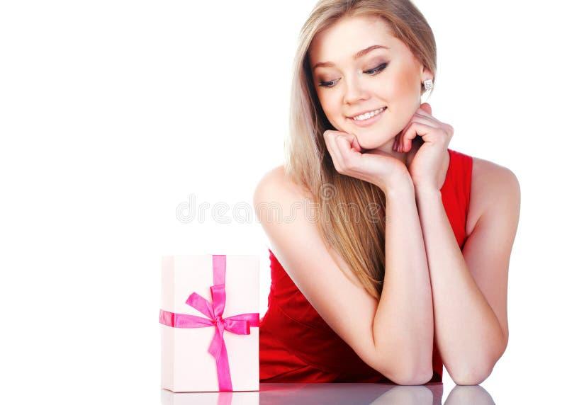 Menina bonita em um vestido vermelho com um presente fotos de stock