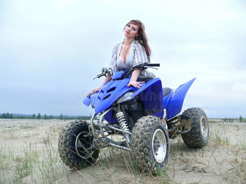 Menina bonita em uma bicicleta do quadrilátero. imagens de stock