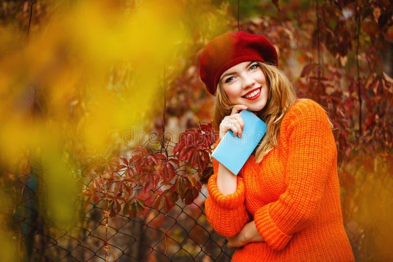 A menina bonita em uma boina e uma camiseta no outono estacionam, guardando um n fotos de stock