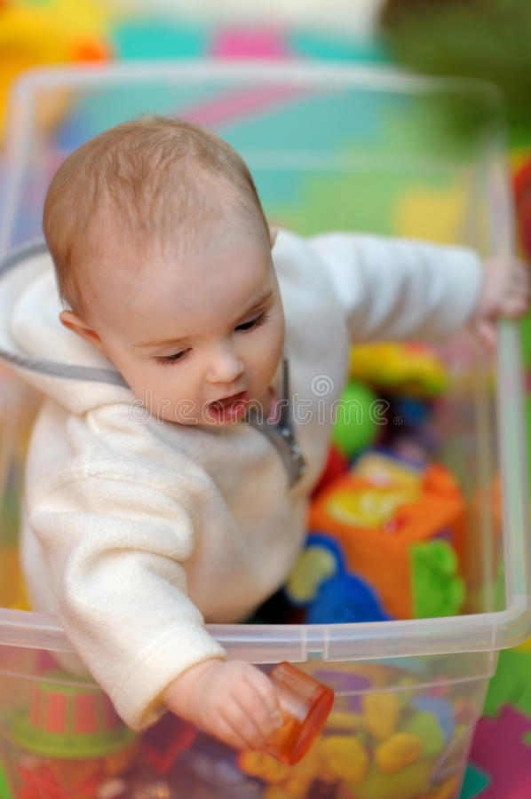 Menina bonita em uma caixa de brinquedo foto de stock