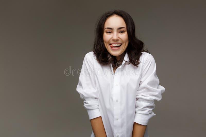 A menina bonita em uma camisa branca mostra emoções - sorriso, divertimento foto de stock royalty free