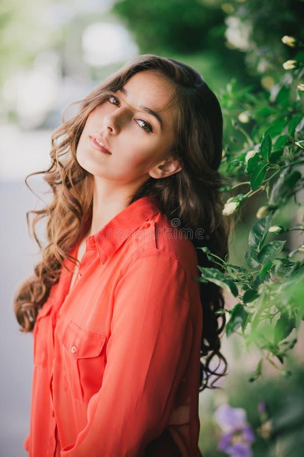 Menina bonita em uma camisa vermelha que levanta em uma rua imagem de stock