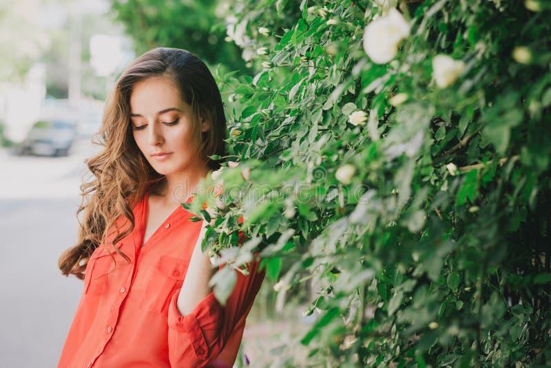 Menina bonita em uma camisa vermelha que levanta em uma rua fotografia de stock