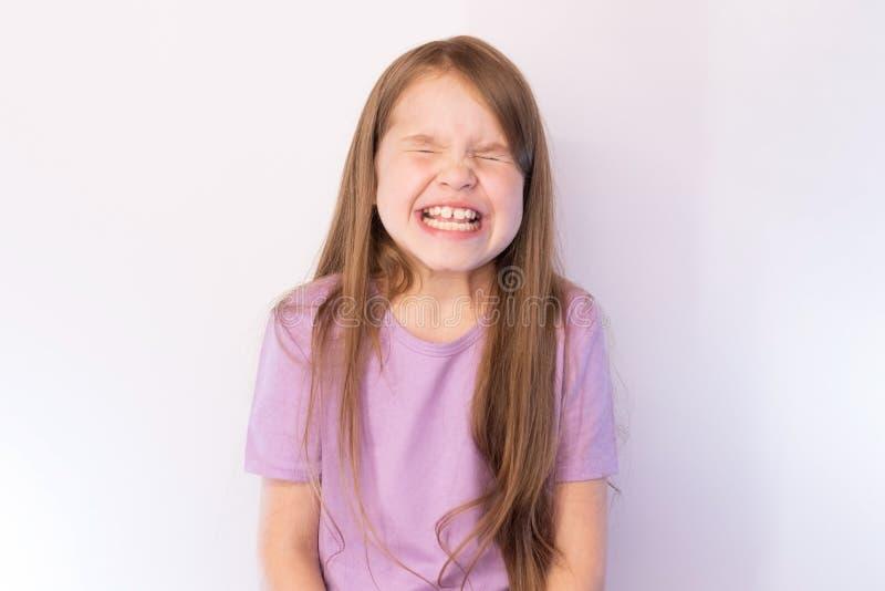 A menina bonita, em uma camiseta lilás e com um cabelo de fluxo, piscando fortemente, mostra os dentes, em um fundo claro fotos de stock royalty free