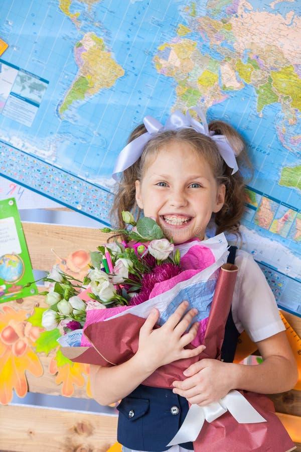 Menina bonita em uma farda da escola perto de uma administração da escola com um ramalhete nas mãos fotos de stock