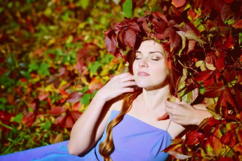 A menina bonita em uma grinalda das folhas de outono está no vermelho, amarelo e folha verde em um dia ensolarado, pensou, e fech fotografia de stock royalty free