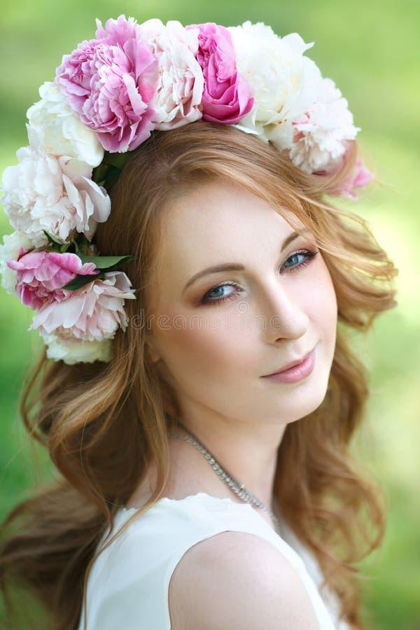 menina bonita em uma grinalda das peônias fotografia de stock