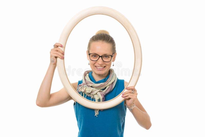 Menina bonita em uma moldura para retrato em um fundo branco fotos de stock royalty free