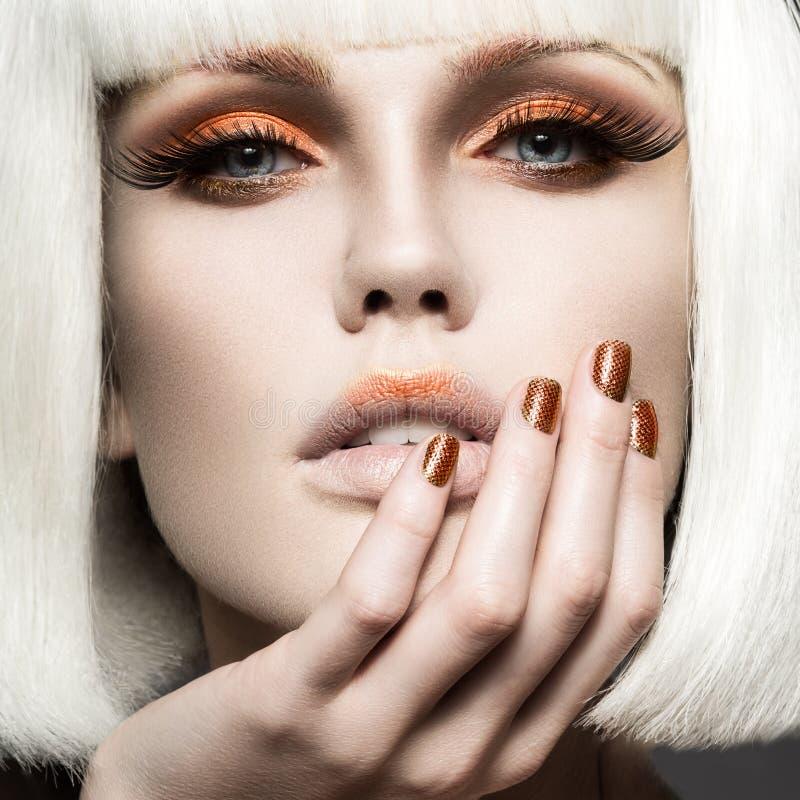Menina bonita em uma peruca branca, com composição do ouro e pregos Imagem comemorativo Face da beleza foto de stock royalty free