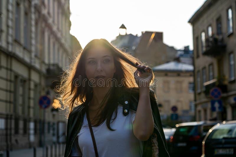 Menina bonita em uma rua da cidade com construções velhas com o luminoso do sol em um cabelo Tiro da foto da forma da rua fotografia de stock royalty free