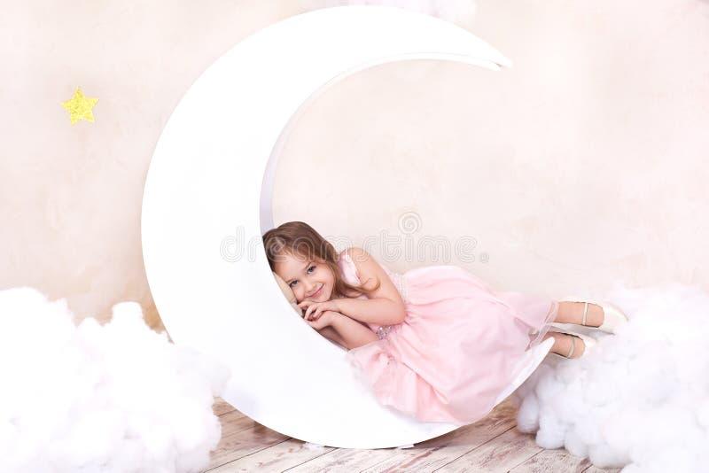 A menina bonita encontra-se no estúdio com a decoração da lua, das estrelas e das nuvens Sonhar pequeno da menina Sonhos doces Po imagens de stock