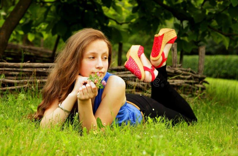 A menina bonita encontra-se no gramado com grama verde e olha-se na distância foto de stock royalty free