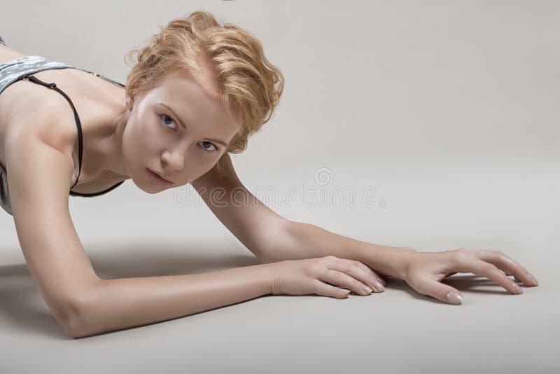 a menina bonita encontra-se sexualmente no assoalho em seu roupa interior foto de stock