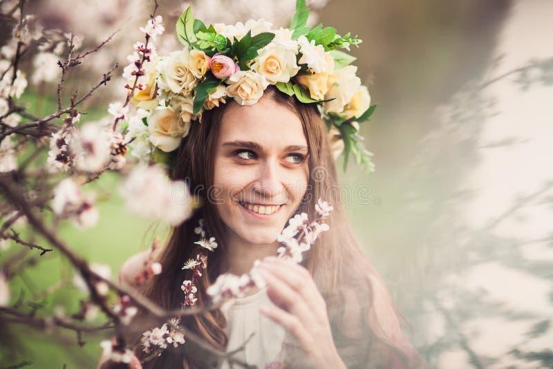 Menina bonita entre os ramos da árvore de cereja da flor foto de stock