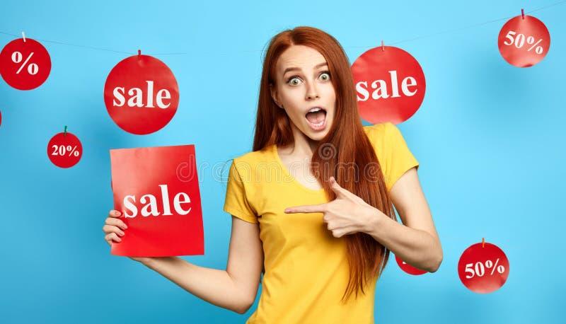 Menina bonita entusiasmado do gengibre que aponta à folha de papel com a venda da palavra fotografia de stock royalty free